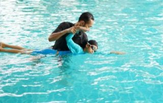 man giving child swimming lessons in a pool